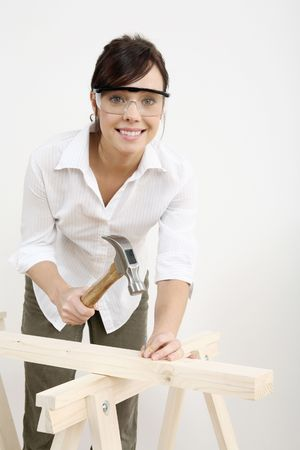 Woman with safety goggles hammering nail into wood Stock Photo - 2966414