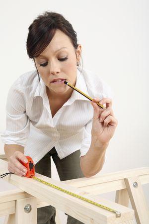 Woman measuring wood 写真素材
