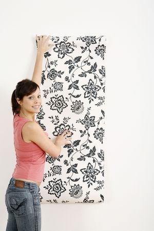 Woman decorating the wall with wallpaper