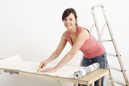 Woman cutting wallpaper Stock Photo - 2966427