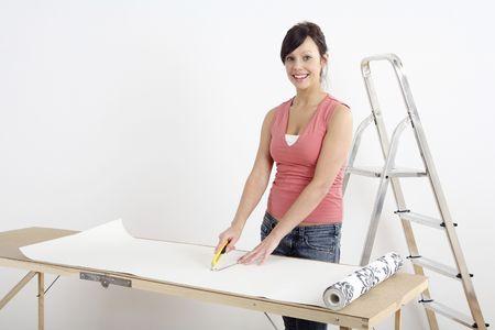 Woman cutting wallpaper photo
