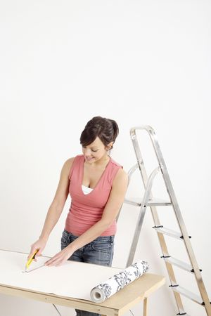 Woman cutting wallpaper Stock Photo - 2966430