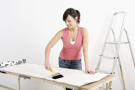 Woman applying glue on wallpaper Stock Photo - 2966431