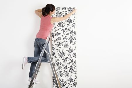 Woman decorating wall with wallpaper