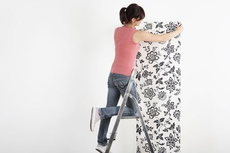 decorating: Woman decorating wall with wallpaper