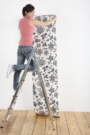 Woman decorating wall with wallpaper Stock Photo - 2966437