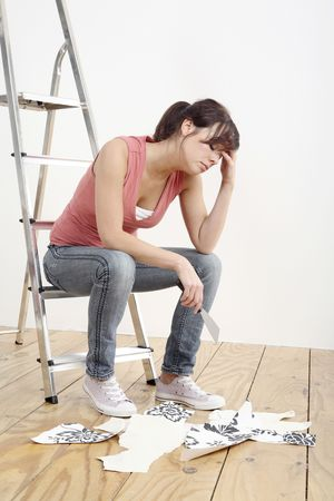 Woman sitting on ladder holding a wallpaper stripper Stock Photo - 2966439