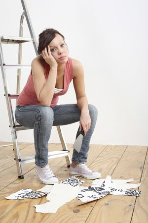 Woman sitting on ladder holding a wallpaper stripper Stock Photo - 2966441
