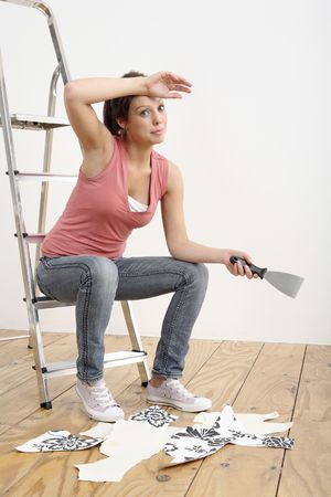 Woman sitting on ladder holding a wallpaper stripper Stock Photo - 2966443