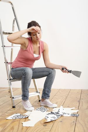 Woman sitting on ladder holding a wallpaper stripper Stock Photo - 2966444