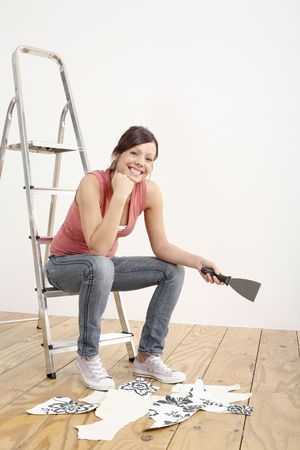 Woman sitting on ladder holding a wallpaper stripper Stock Photo - 2966446
