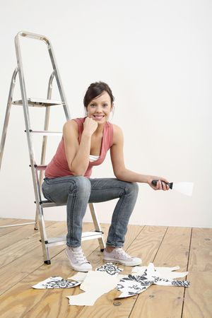 Woman sitting on ladder holding a wallpaper stripper Stock Photo - 2966447