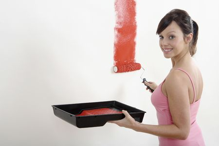 painting: Woman painting wall with paint roller