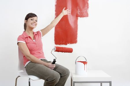 adult wall: Woman showing the half painted wall while holding paint roller