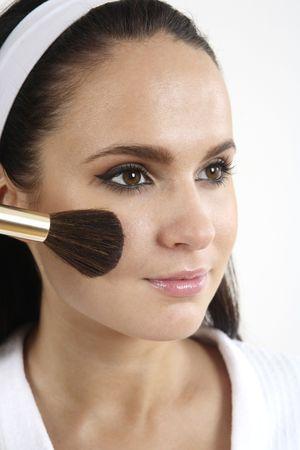 Mujer que aplica el blusher en sus mejillas Foto de archivo - 2966501