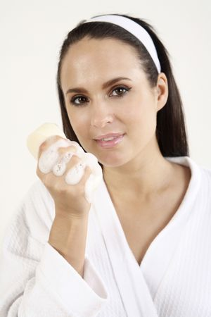 Woman in bathrobe holding a sponge with soap suds Stock Photo - 2966520