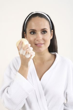 Woman in bathrobe holding a sponge with soap suds Stock Photo - 2966521