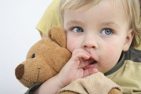 幼児が彼の口に彼の指で彼の柔らかいおもちゃを保持