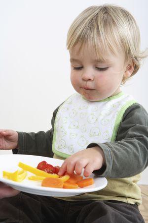 eating: Preschooler with  bib eating vegetables LANG_EVOIMAGES