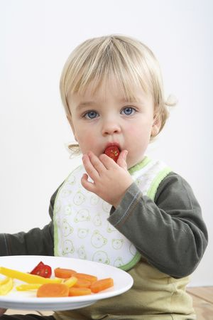 Preschooler with  bib eating vegetables Stock Photo - 2966580