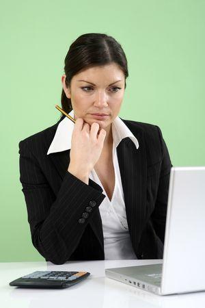 Businesswoman thinking while using laptop Stock Photo