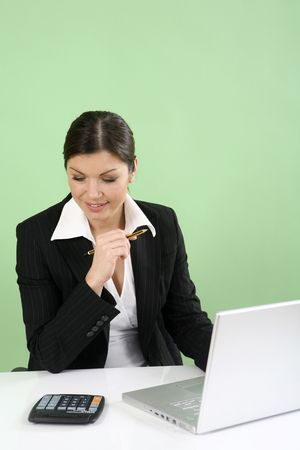Businesswoman doing calculation while using laptop photo