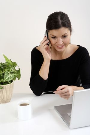 Businesswoman holding credit card while talking on the phone photo
