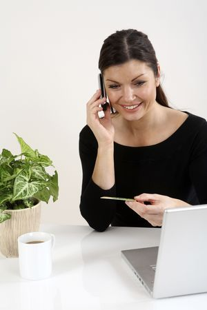 Businesswoman holding credit card while talking on the phone Stock Photo - 3198866