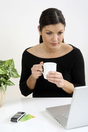 Businesswoman holding a cup while using laptop Stock Photo - 3198852