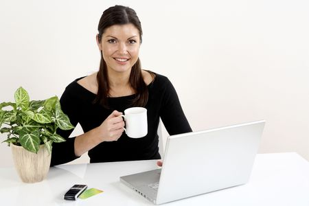 Businesswoman holding a cup while using laptop Stock Photo - 3198792