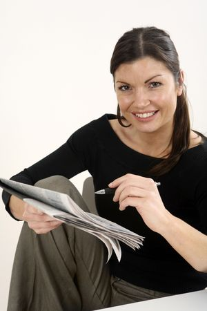 Businesswoman holding pen while reading newspaper photo
