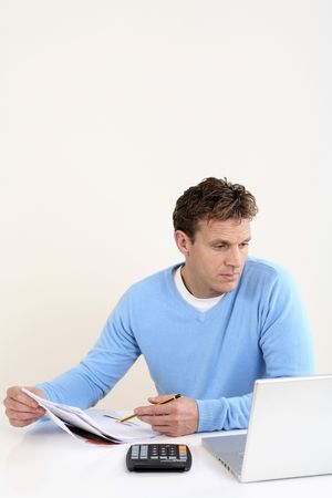 Man referring to laptop while holding pen and paper