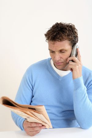 Man reading newspaper while talking on the phone photo