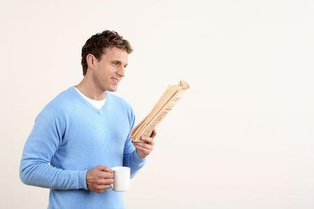 El hombre la celebraci�n de una taza al leer el peri�dico