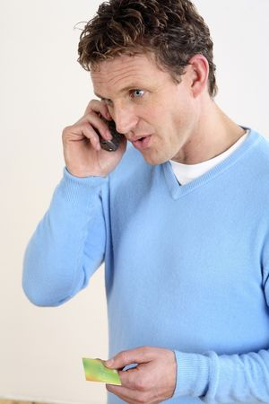call: Man holding credit card while making a call Stock Photo