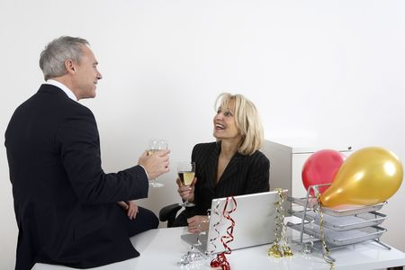 Businessman and businesswoman chatting while enjoying their drinks photo