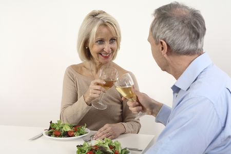 Man and woman toasting drinks while having dinner together photo