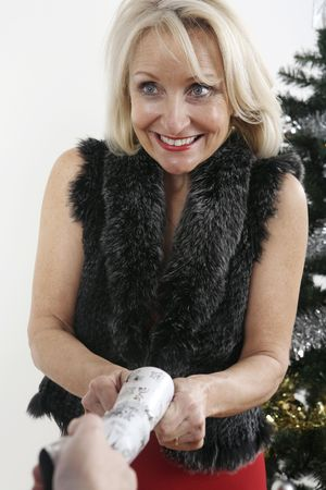 Woman pulling christmas cracker Stock Photo - 3200352