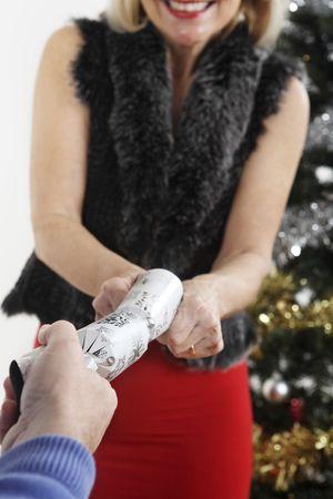 Woman pulling christmas cracker Stock Photo - 3200326