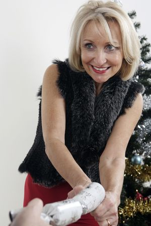 Woman pulling christmas cracker photo