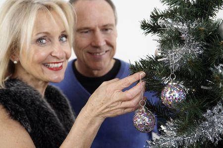 Woman decorating christmas tree, man watching photo