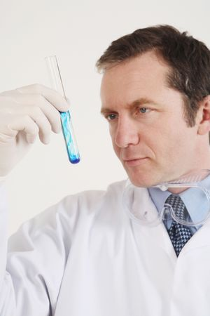 Man examining liquid in a test tube photo
