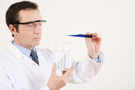 testtube: Man pouring liquid from a test tube into a beaker Stock Photo
