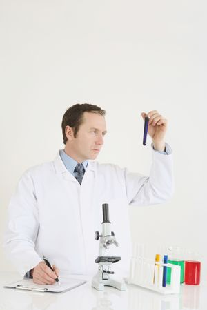 scrutiny: Man writing results of science experiment Stock Photo