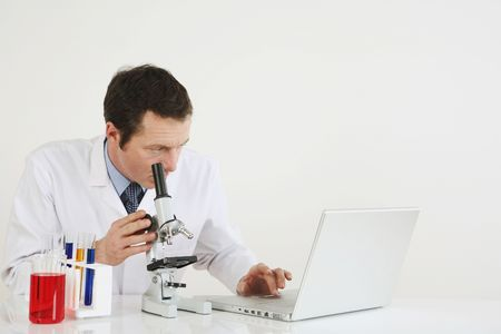 ラップトップと顕微鏡を使用して男