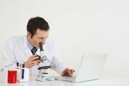 Hombre utilizando port�tiles y microscopio  Foto de archivo