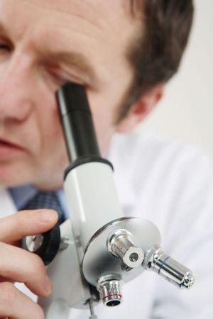 Hombre utilizando microscopio  Foto de archivo