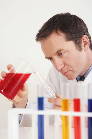 Man pouring liquid from beaker into test tube photo