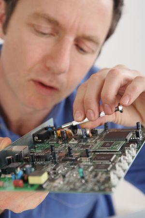 El hombre la reparación de una computadora placa de circuito  Foto de archivo