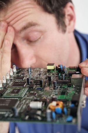 teknik: Man getting a headache from repairing a computer circuit board